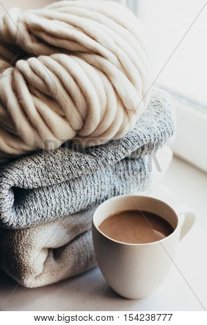 Stack of cozy knitted sweaters and thick yarn on window sill. Morning coffee in lazy winter weekend.