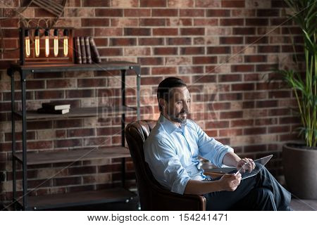 Being at the office. Pleasant joyful self employed man holding a tablet and working on it while sitting in the leather armchair