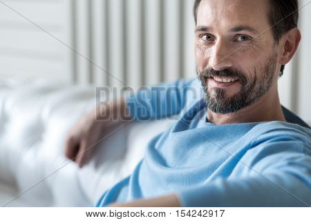 Cheerful face. Optimistic good looking confident man sitting on a white sofa and smiling while being in a good mood