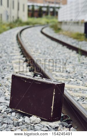 an old brown suitcase next to the railroad tracks