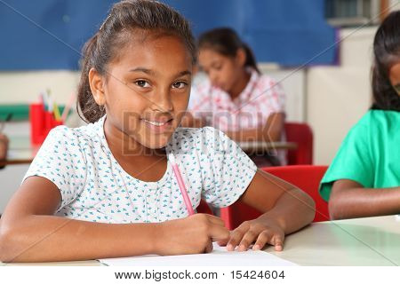 Primary schoolgirl looks up from work in classroom