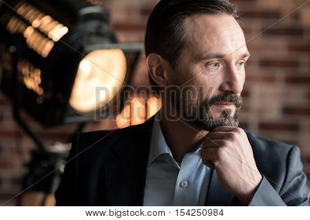 Thoughtful look. Handsome thoughtful bearded businessman holding his chin and looking to the left while thinking about something