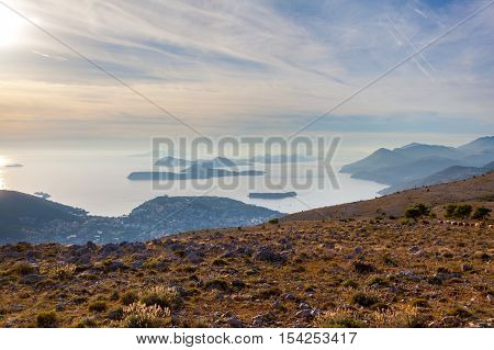 Sunset on the Adriatic sea with layers mountains on the horizon. Misty layers of mountains. Beautiful hills, growing out of the water in the evening. The islands in the sea. Dubrovnik. Croatia.