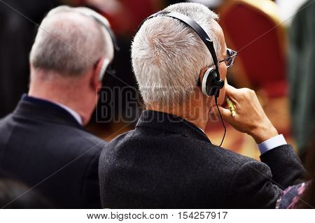 Unrecognizable person using in ear headphones for translation during event