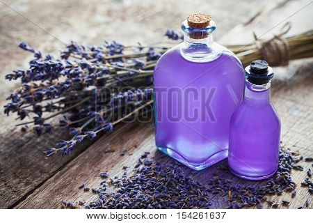 Bottles of essential oil and lavender flowers bunch on table. Retro toned. Selective focus.