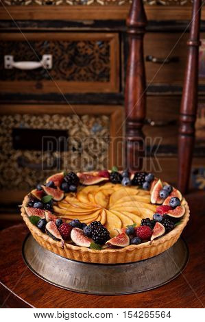 Traditional french apple tart decorated with fresh fruit and berries