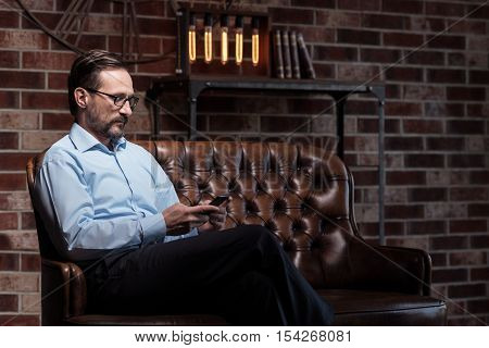 Always online. Nice serious self employed man holding his smartphone and typing a message while sitting on the sofa