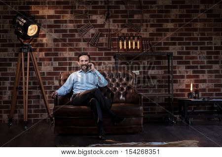 Feeling comfortable. Handsome joyful self employed man sitting on the couch and talking on the phone while looking in front of him