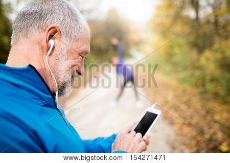Senior runners in nature, stretching. Man with smart phone with earphones. Listening music or using a fitness app. Using phone app for tracking weight loss progress, running goal or summary of his run.