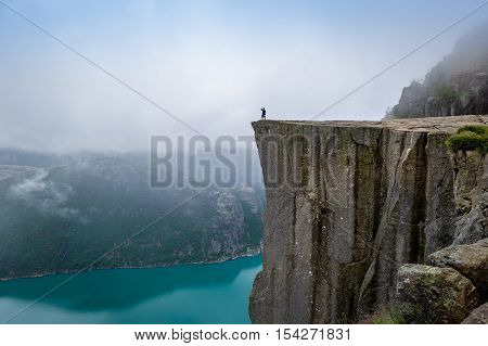 Tourist is standing at the cliff of famous norwegian touristic attraction - Prekestolen rock. Lysefjord, Rogaland, Norway.