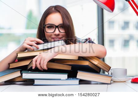 Young woman student with many books