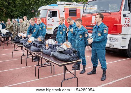 MOSCOW, RUSSIA - AUG 20, 2016: Teams of firefighters stand next to the fire trucks and tables with clothes during the Moscow City Championship of combat deployment in Luzhniki.