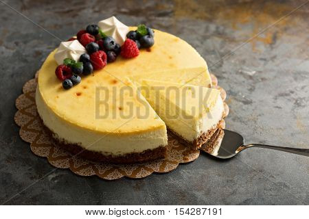 Homemade New York cheesecake on a cake stand decorated with fresh berries