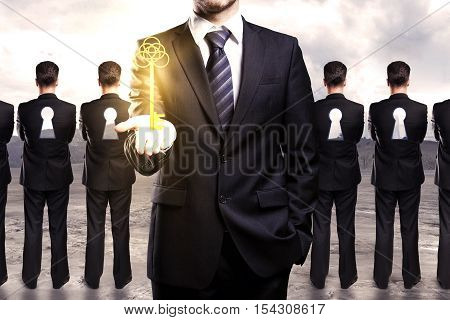Businessman holding ornate golden key. Row of businessmen with keyholes in backs on landscape background. Right approach ethics concept