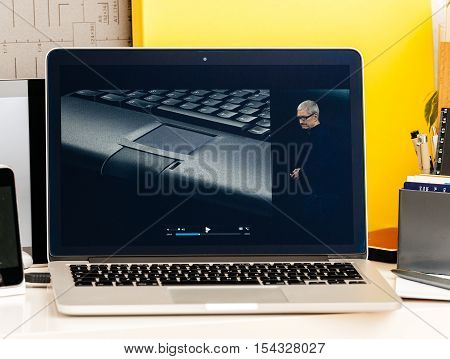 PARIS FRANCE - OCT 28 2016: Apple Computers website on new MacBook Pro Retina with OLED Touch bar in geek creative room showcasing Apple Keynote - history of Macitosh PowerBook laptop and Tim Cook