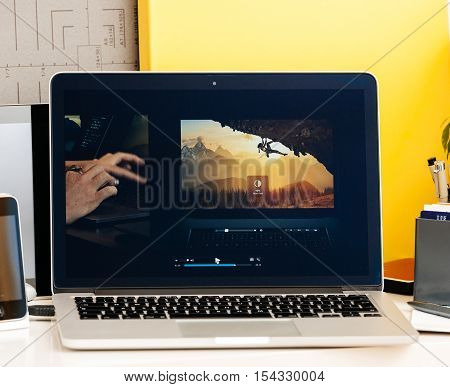PARIS FRANCE - OCT 28 2016: Apple Computers website on new MacBook Pro Retina with OLED Touch bar in geek creative room showcasing Apple Keynote presentation of Bradee Evans from Adobe OLED Photoshop inegration