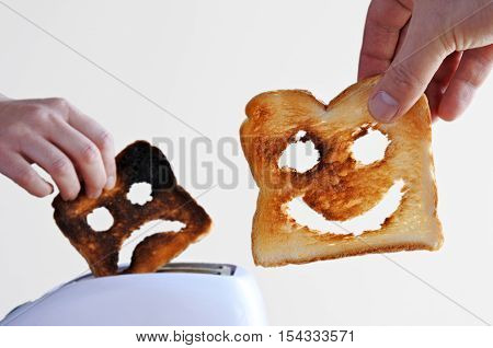 Man hand holds one slices of toast bread with happy face against a toaster and woman hand holds a burnt toast with sad face.Couple relationship concept. copy space