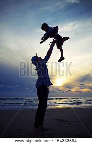 Mid low angle shot of the father who is tossing up a child at the sunset on the beach