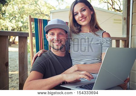 An attractive young couple relaxing together in their rest summer house. The woman is sitting on the man's lap and they are smiling at the camera happily