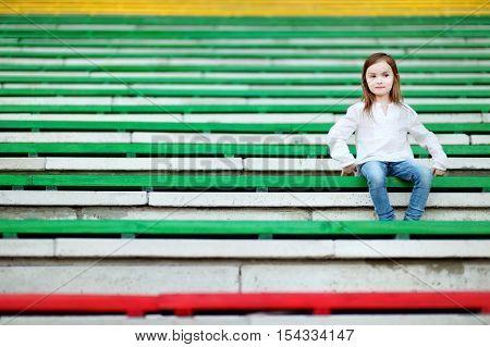 Cute Girl Sitting On A Stadium Seat