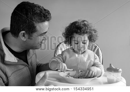 Father (man age 35-45) takes care of his child (girl age 2-3) at meal time. Fatherhood parenting and childhood concept. Real people copy space