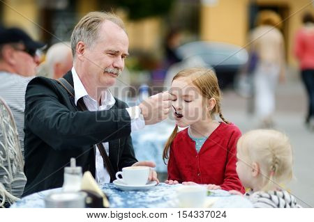 Grandfather feeding frothy milk to his grandchild at summer cafe on beautiful sunny day
