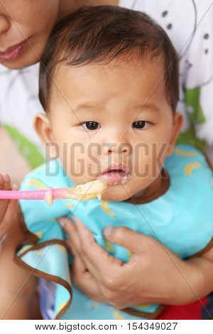 Asian baby boy to eating food in concept of health foods and nutrition for development and growth.