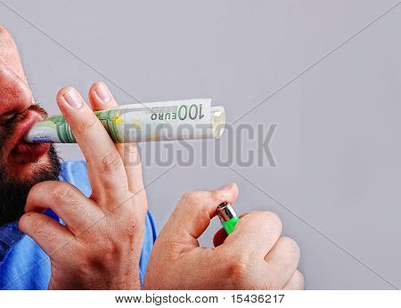 Man is taking paper money as a cigarette