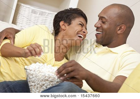 Happy African American Couple Eating Popcorn Watching Movie At Home