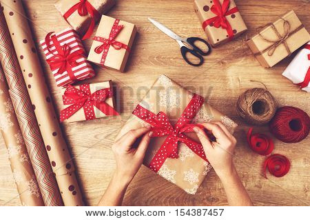 hand of woman packs boxes with Christmas gifts presents on a wooden table