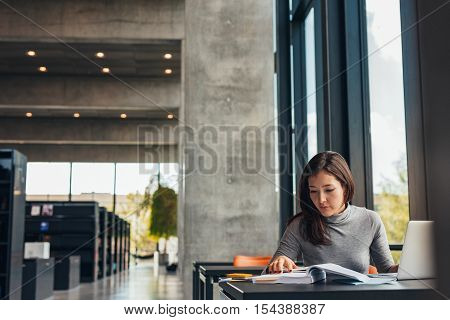 Indoor shot of young female student doing assignments in library. Asian woman reading textbook while sitting at college library.
