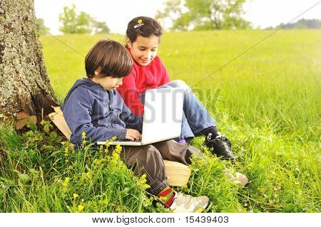 Happy childhood in nature, beautiful scene with laptop under the tree