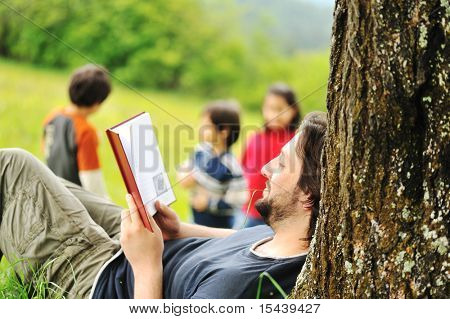 Young relaxed father reading book and children playing around