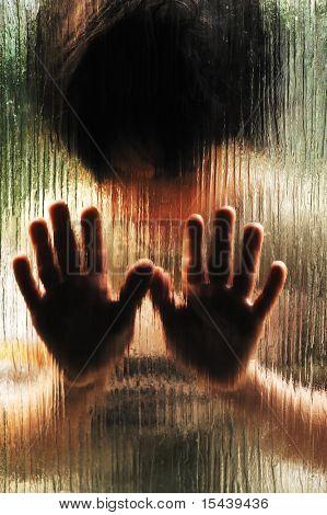 Silueta de niño maltratado tras el cristal
