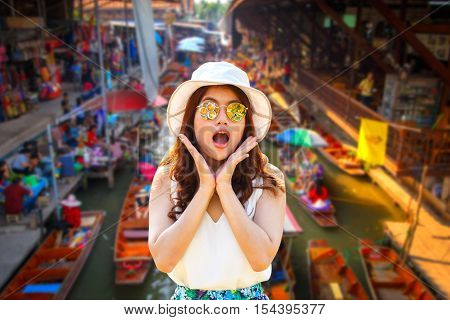 Wow. Close up portrait young asian woman beautiful girl with long red hair looking excited holding her mouth opened amazing thai culture Damnoen Saduak floating market in Ratchaburi near Bangkok Thailand