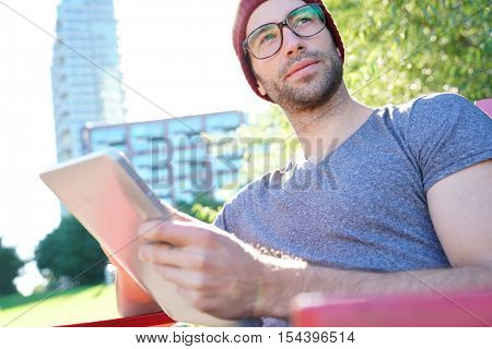 Hipster guy in park websurfing on digital tablet