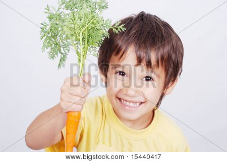 Boy eating fresh carrots isolated on white background