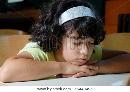 Young Girl Asleep on Book at Desk in School