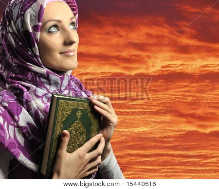 Adorable Muslim girl holding holy book Koran, against red sky
