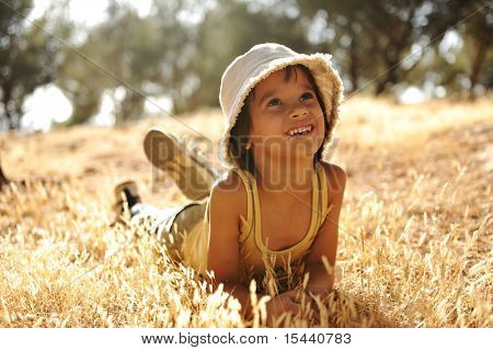 Careless boy on yellow grass meadow in autumn