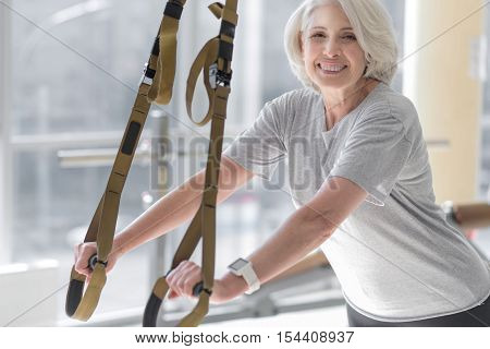 Description: Something new. Active pretty senior woman using special equipment and smiling while spending time in a gym.