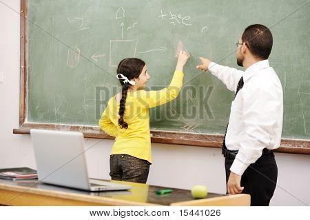 Teacher helping schoolgirl in front of board