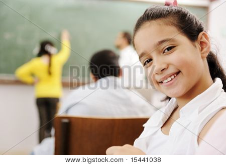 Adorable girl smiling in school classroom and behind her class activities