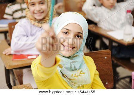 Liebenswert muslimisches Mädchen im Klassenzimmer mit ihren Freunden-Kinder-Schülern