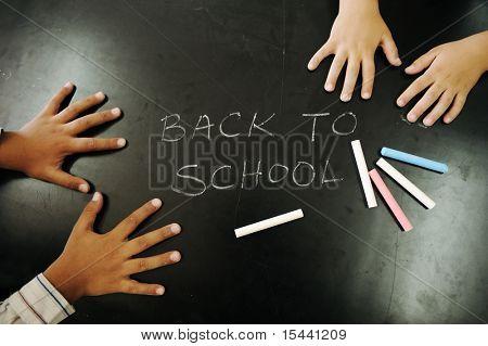 Multiraces Kinder Hände auf Tafel mit Kreide: zurück in die Schule!