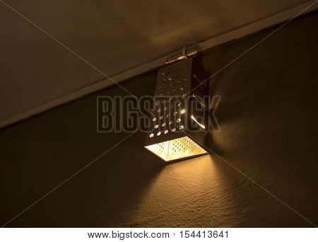 Warm lighting coming out from beautiful home made diy kitchen grater and lamps on wall