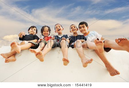 Five happy friends sitting on wall outdoor