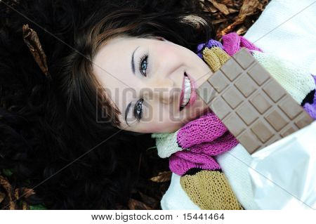 Close-up portrait of an beautiful autumn woman laying on fall leafs  and eating chocolate
