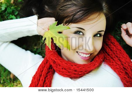 Close-up portrait of an beautiful autumn woman laying on ground with leave in hand