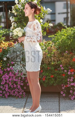 A full-body portrait of a happy new bride keeps her bridal bouquet on the happiest day of their lives - side view